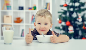 Mała chłopiec je i pokazuje aprobaty Obraz Stock