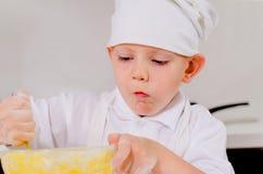 Mała chłopiec miesza składniki dla torta w pucharze Obraz Stock