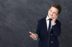 Mała chłopiec opowiada na telefonie komórkowym w kostiumu fotografia royalty free