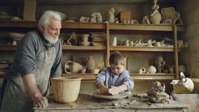 Mała chłopiec pleśnieje clayware w jego dziadu ` s studiu podczas gdy jego troskliwy starszy dziadunio jest trwanie pobliski on i zdjęcie wideo