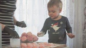 Mała chłopiec pomaga jego matki gotować wpólnie w kuchennych marshmallows dla boże narodzenie gościa restauracji w zwolnionym tem zbiory wideo