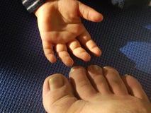 Mała chłopiec ręka obok brudnej męskiej stopy Obrazy Stock