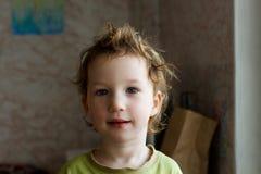 Mała chłopiec siedzi blisko okno i główkowania o coś Pięknego wielkiego włosy słodkie dziecko Zdjęcie Stock