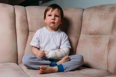 Mała chłopiec siedzi na krześle z łamaną ręką w lanym szpitalu, Medycyna niebezpieczeństwo ból łamać kończyny brutalnie fotografia stock