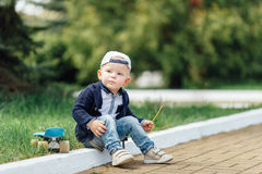 Mała chłopiec siedzi przy plamy zieleni tłem Zdjęcie Royalty Free