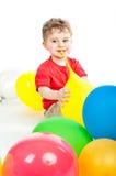 Mała chłopiec siedzi wokoło balonów Zdjęcia Royalty Free