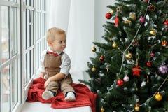 Mała chłopiec sittiing blisko nadokiennego i patrzeje na choince Wakacje, prezent i nowego roku pojęcie, Fotografia Stock