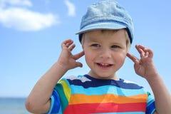 Mała chłopiec trzyma jego ręki nad ucho no słuchać obraz royalty free