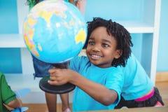 Mała chłopiec trzyma kulę ziemską świat Zdjęcia Royalty Free
