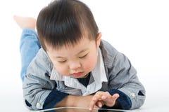 Mała chłopiec używa pastylkę obraz royalty free