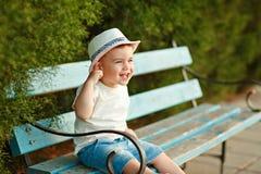 Mała chłopiec w kapeluszowym obsiadaniu na ławce w ch i lecie Fotografia Royalty Free
