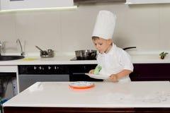 Mała chłopiec w szefa kuchni obcierania jednolitych naczyniach zdjęcia royalty free