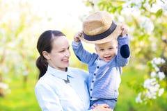 Mała chłopiec z matką w kwitnie ogródzie Zdjęcia Royalty Free