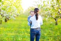 Mała chłopiec z matką w kwitnie ogródzie Zdjęcie Stock