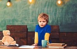 Mała chłopiec z poważną twarzy pozycją za ciemnym drewnianym stołem Skoncentrowany dzieciak opiera na stole Dzieciak udaje zdjęcie stock