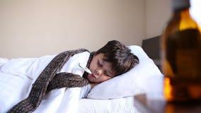 Mała chora chłopiec z cyfrowym termometrem zbiory