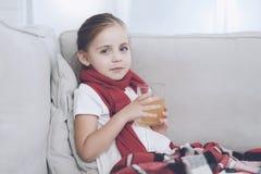 Mała chora dziewczyna siedzi na białej leżance zawijającej w czerwonym szaliku Siedzi z filiżanką lecznicza herbata zdjęcia royalty free
