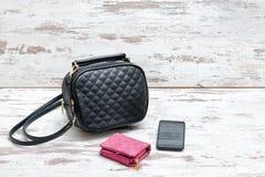 Mała czarna damy torebka, różowa kiesa i mądrze telefon na woode, zdjęcia stock