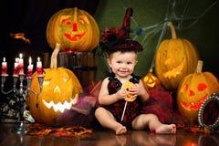 Mała czarownica śmia się z cukierkiem w rękach wśród świeczek i bani Obraz Stock