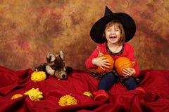 Mała czarownica ma zabawę dla Halloween z baniami i kapeluszem Zdjęcie Stock