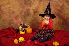 Mała czarownica ma zabawę dla Halloween z baniami i kapeluszem Zdjęcia Stock