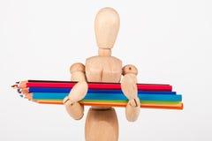 Mała drewniana mannequin pozycja z colour ołówkami Zdjęcia Stock