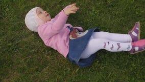Mała dwuletnia piękna dziewczyna w kapeluszu siedzi na zielonej trawie na letnim dniu zbiory