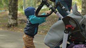 Mała dziecko berbecia chłopiec pcha fracht w zdjęcie wideo