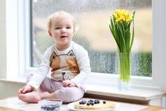 Mała dziewczyna bawić się indoors jeść smakowitych bliny Zdjęcie Royalty Free