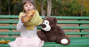 Mała dziewczyna je galonową babeczkę z maczkiem na ławce z misiem przy boiskiem w jesień parku zbiory