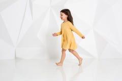 Mała dziewczyna jest ubranym koloru żółtego smokingowego tana w studiu przeciw białemu tłu Zdjęcie Stock
