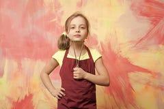 Mała dziewczyna lub dziecko w kucbarskim fartuchu z potatoe masher obraz royalty free