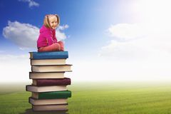 Mała dziewczyna siedzi na stosie książki Fotografia Royalty Free