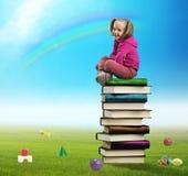Mała dziewczyna siedzi na stosie książki zdjęcie stock