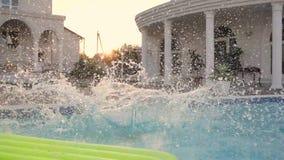 Mała dziewczyna skacze w basenie, dzieciaka skok z pluśnięciem w pływackim basenie, słodki żeński dziecko na wakacje blisko basen zdjęcie wideo