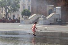Mała dziewczyna używa wodną zasłonę w pogodnym gorącym dniu, Krakow, Polska Zdjęcia Royalty Free