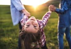 Mała dziewczyna z jej starszymi dziadkami ma zabawę outside w naturze przy zmierzchem Obrazy Stock