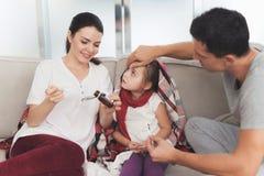 Mała dziewczynka łapał zimno Jej ojciec i matka taktujemy ona Matka nalewa dziewczyna syrop w łyżkę obrazy royalty free