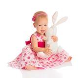Mała dziewczynka ściska zabawkarskiego królika królika na bielu Zdjęcia Stock