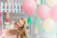 Mała dziewczynka śmia się i skacze w studiu z balonami Zdjęcie Royalty Free