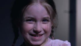 Mała dziewczynka śmia się szczerze w kamerę, beztroski dziecko cieszy się życia zbliżenie zdjęcie wideo