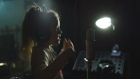 Mała dziewczynka śpiew w mikrofon w studiu nagrań zbiory wideo