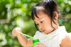Mała dziewczynka bawić się bąbel dmuchawę Obraz Stock