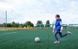 Mała dziewczynka bawić się futbol na boisku piłkarskim z sztuczną murawą plenerową zdjęcie stock