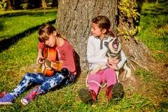 Mała dziewczynka bawić się gitarę w parku z łuskowatym szczeniaka śpiewem Zdjęcia Stock