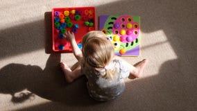 Mała dziewczynka bawić się grę rozwijać motorowe umiejętności, zbiera projektant multicolor mozaikę dla dzieci, rozwój g zbiory