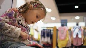 Mała dziewczynka bawić się grę używać smartphone w sklepie zbiory wideo