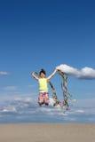 Mała dziewczynka bawić się i skacze na plaży Obrazy Royalty Free