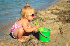 Mała dziewczynka bawić się na plaży z pail i łopatą Obrazy Royalty Free