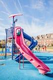 Mała dziewczynka bawić się na wysokim obruszeniu przy dziecka boiskiem Obrazy Stock